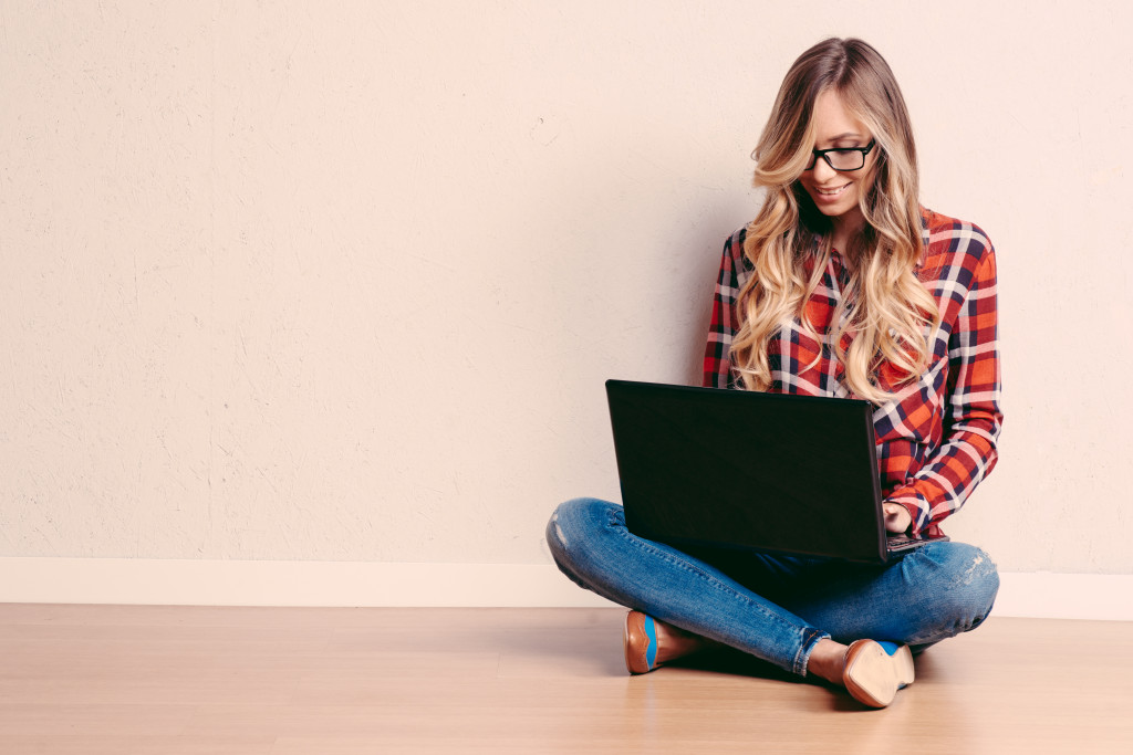 Young creative woman sitting in the floor with laptop.